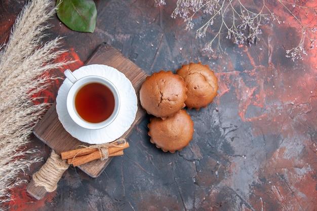 Nahaufnahme von oben eine tasse tee eine tasse tee zimtstangen auf dem brett zitrusfrüchte