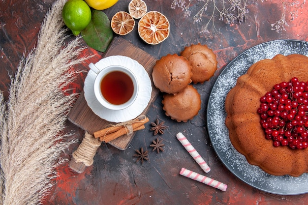 Nahaufnahme von oben eine tasse tee einen kuchen mit roten johannisbeeren eine tasse tee auf dem schneidebrett