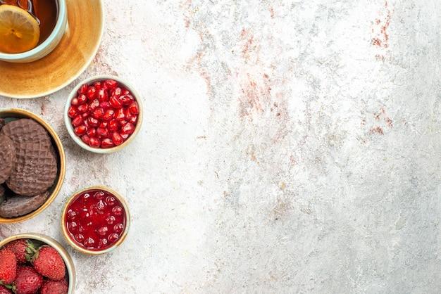 Nahaufnahme von oben eine tasse tee granatapfelmarmelade eine tasse tee mit zimt-schokoladenkeksen