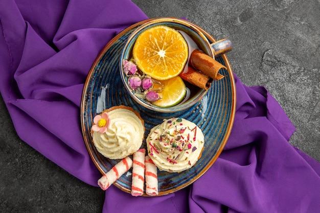 Nahaufnahme von oben eine tasse tee mit appetitlichen cupcakes mit zitrone mit einer tasse tee auf der lila tischdecke auf dem tisch
