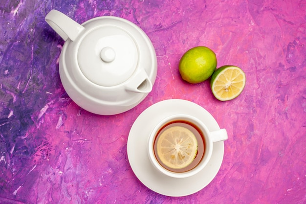 Nahaufnahme von oben eine tasse tee weiße teekanne eine tasse schwarzen tee und limetten auf dem rosa tisch
