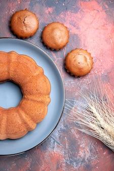 Nahaufnahme von oben einen blauen kuchenteller mit drei appetitlichen cupcakes und weizenähren