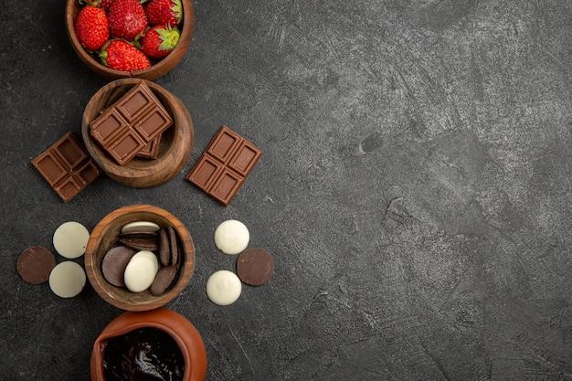 Nahaufnahme von oben erdbeeren und schokolade erdbeeren schokolade und schokoladensauce in schalen auf der linken seite des tisches