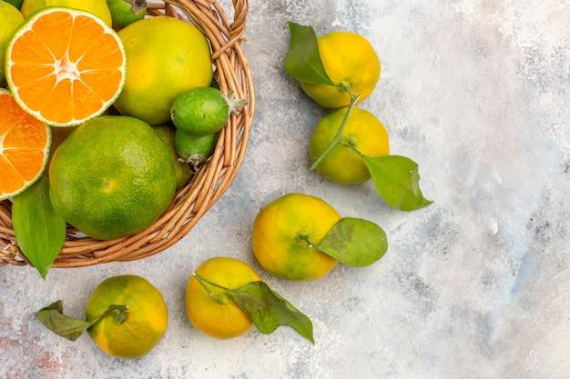 Nahaufnahme von oben frische mandarinen im weidenkorb, umgeben von mandarinen auf nacktem hintergrund