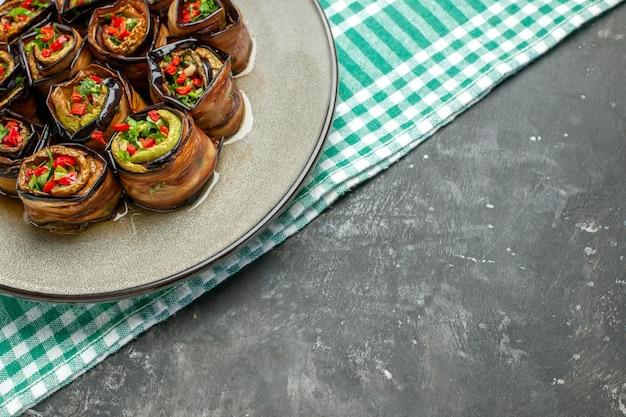 Nahaufnahme von oben gefüllte auberginenröllchen in weißer ovaler platte türkis-weißer tischdecke auf grauem hintergrund