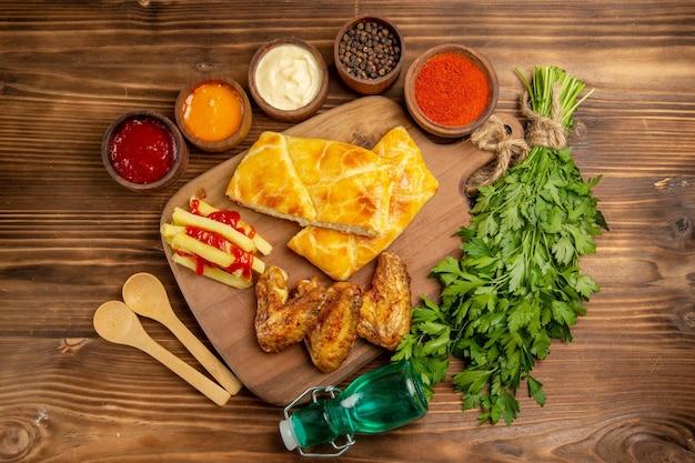 Nahaufnahme von oben gewürzsaucen hühnerflügel pommes frites mit ketchup und kuchen auf dem küchenbrett neben den schüsseln mit bunten gewürzen und saucen holzlöffel kräuter und flasche