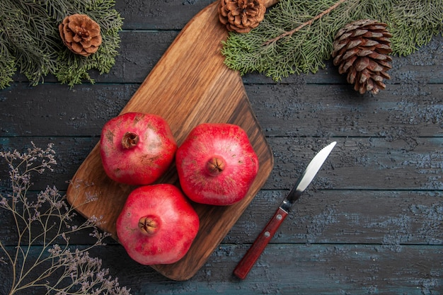 Nahaufnahme von oben granatäpfel an bord granatäpfel auf schneidebrett neben messer- und fichtenzweigen mit zapfen