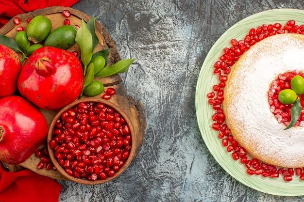 Nahaufnahme von oben granatäpfel einen appetitlichen kuchen und rote granatäpfel auf der roten tischdecke