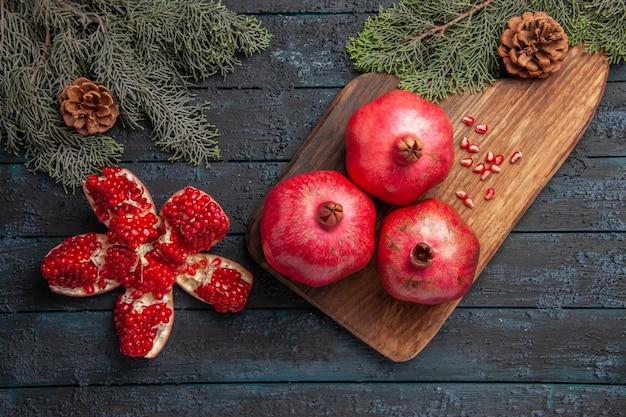 Nahaufnahme von oben granatapfel an bord drei reife granatäpfel auf holzbrett neben samen von granatapfel-fichtenzweigen mit zapfen und gepilltem granatapfel auf dem tisch