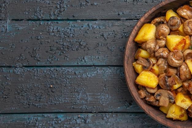 Nahaufnahme von oben kartoffeln mit pilzen braune schüssel mit kartoffeln und pilzen auf der rechten seite des tisches