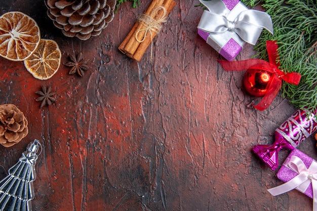 Nahaufnahme von oben kiefer zweige kegel weihnachtsbaum spielzeug zimt getrocknete zitronenscheiben sternanis auf dunkelrotem hintergrund