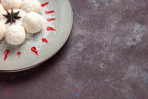 Nahaufnahme von oben leckere kokosbonbons mit rotem zuckerguss auf dunklem raum