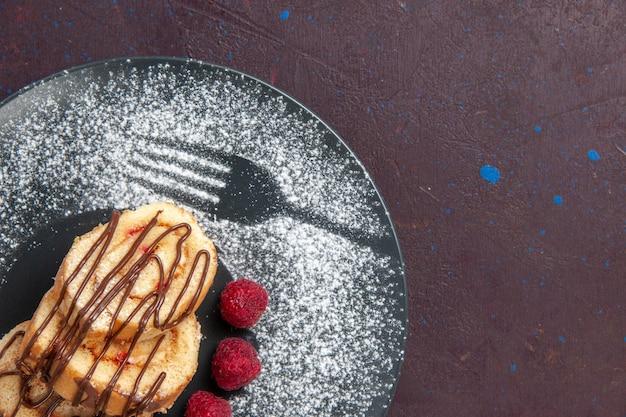 Nahaufnahme von oben leckere süße brötchen in scheiben geschnittenen kuchen für tee im teller auf dunklem raum