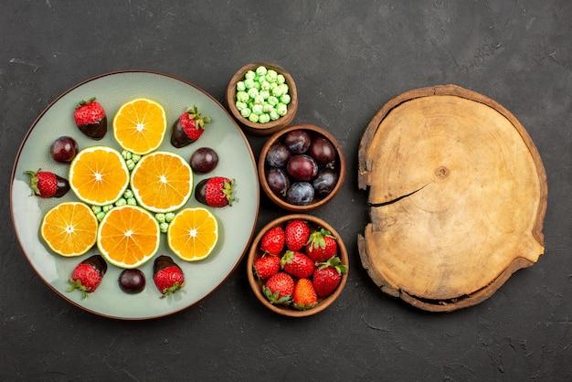 Nahaufnahme von oben mit schokolade überzogene erdbeere gehackte orange schokolade überzogene erdbeere und grüne süßigkeiten und schalen mit verschiedenen früchten, beeren und süßigkeiten neben dem holzbrett