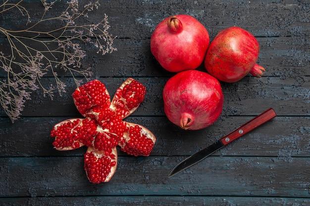 Nahaufnahme von oben reife granatäpfel reifer gepillter granatapfel zwischen drei granatapfelbaumzweigen und messer auf dunklem hintergrund