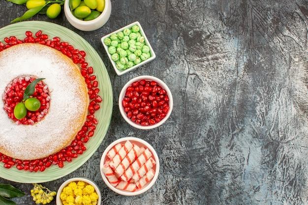 Nahaufnahme von oben süßigkeiten ein appetitlicher kuchen mit samen von granatäpfeln, zitrusfrüchten und bonbons