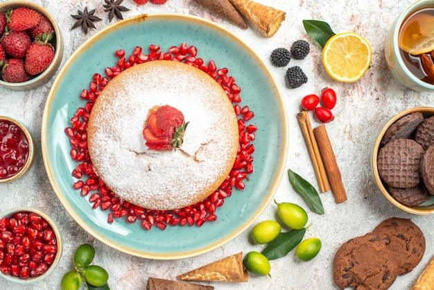 Nahaufnahme von oben süßigkeiten schokoladenkekse eine tasse tee mit zitrone ein kuchen zimt beeren limetten