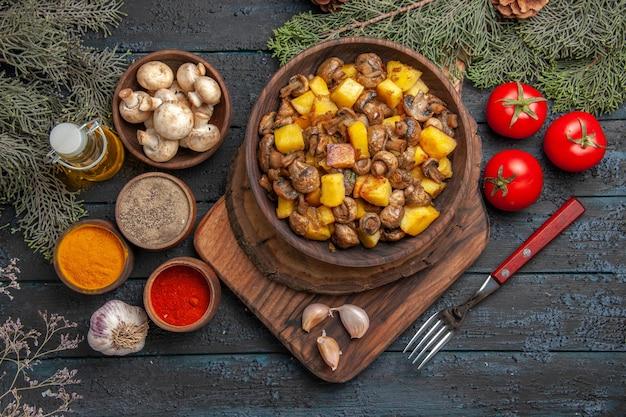 Nahaufnahme von oben teller und gewürzteller kartoffeln mit pilzen auf holzbrett cutting
