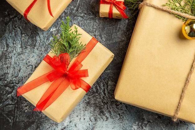 Nahaufnahme von oben weihnachtsgeschenk kleine geschenke tannenzweige auf grauem hintergrund