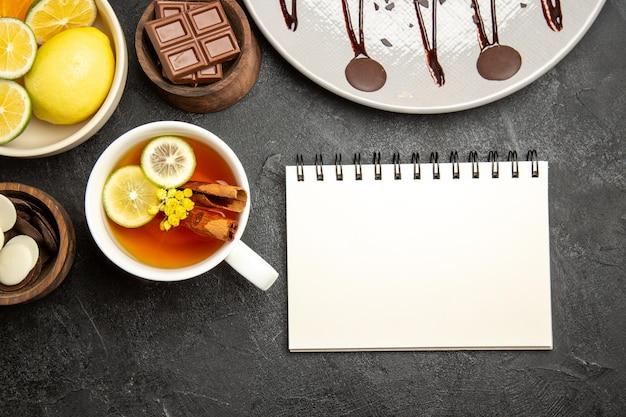 Nahaufnahme von oben zitrusfrüchte schokoladenschalen mit zitrusfrüchten und schokolade neben dem weißen notizbuch und einer tasse tee mit zitrone