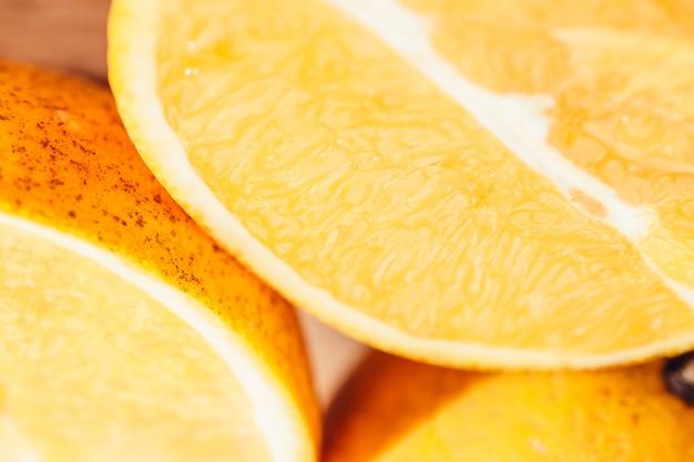 Nahaufnahme von orangenscheiben auf einem holzschneidebrett in der küche in der sonne mit einem scharfen kontrast von licht und schatten in hellen, lebendigen und warmen farben.