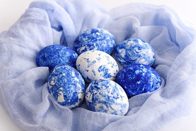 Nahaufnahme von ostereiern in der farbe des jahresklassikers blau mit verlaufseffekt im weichen blauen netzhandtuch, osterkonzept