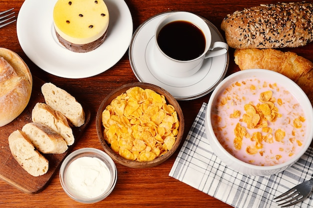 Nahaufnahme von passionsfrucht kuchen, toast, kaffee, joghurt, müsli.