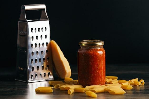 Nahaufnahme von penne pasta und einem glas sauce auf dem tisch mit käse und einer reibe auf dem hintergrund
