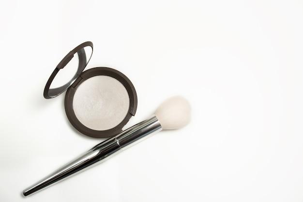 Nahaufnahme von perlen-highlighter mit make-up-pinsel auf weißem hintergrund