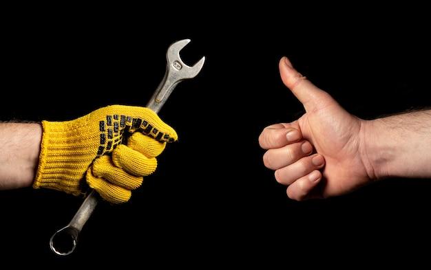 Nahaufnahme von personenhänden, einer hält einen schraubenschlüssel und der andere zeigt ein ok-zeichen.