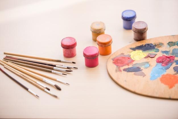 Nahaufnahme von pinseln, von farben und von palette auf dem tisch.