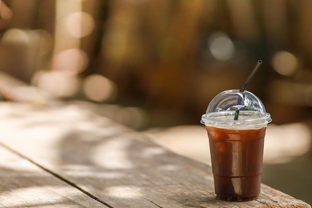 Nahaufnahme von plastikbecher zum mitnehmen des schwarzen eiskaffee-americano auf holztisch mit kopienraum.