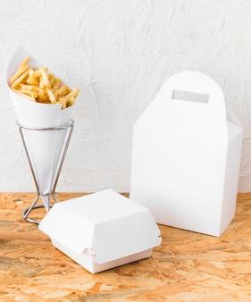 Nahaufnahme von pommes-frites und von lebensmittelpaketspott oben auf hölzernem schreibtisch