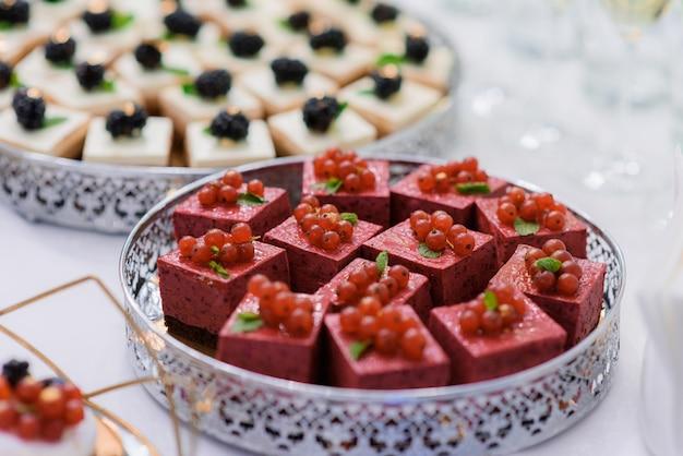 Nahaufnahme von portion mousses desserts mit roten johannisbeeren dekoriert