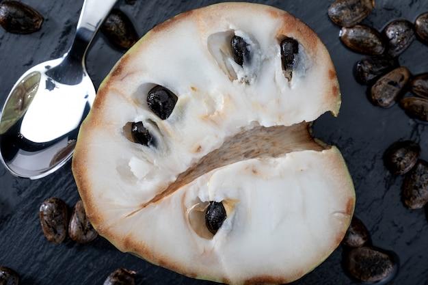 Nahaufnahme von reifen cherimoyas. offenes obst mit nuggets und löffel in der dunkelheit.