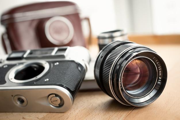 Nahaufnahme von retro-kamera, objektiv und ledertasche auf holztisch liegend