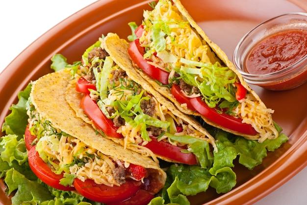 Nahaufnahme von rindfleisch-tacos mit salat und frischen tomaten-salsa auf weißem hintergrund