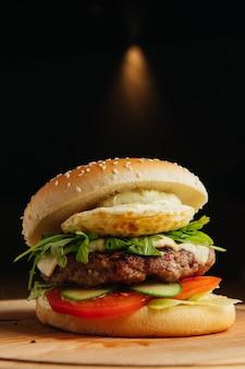 Nahaufnahme von rindfleischburger mit pochiertem ei. hamburger - brötchen, gegrillter fleischburger, rucola-salat, tomate und spiegelei.