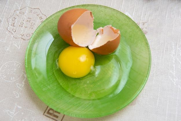 Nahaufnahme von rohem gebrochenem ei roh in einem grünen teller auf dem küchentisch, ansicht von oben. gelbes eigelb und flüssiges eiweiß. zutat zum backen, omelett oder omelett