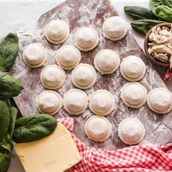 Nahaufnahme von rohen ravioli wischte mit mehl auf hölzernem brett mit bestandteilen ab