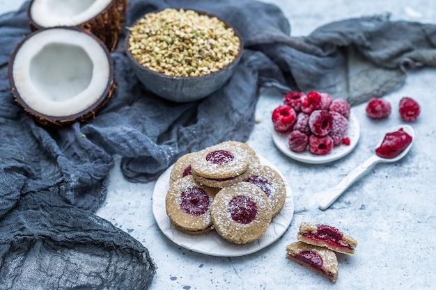 Nahaufnahme von rohen veganen keksen mit kokos und himbeeren