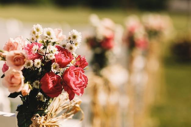 Nahaufnahme von rosa rosen setzte einen blumenstrauß ein, der mit einem stuhl gebunden wurde
