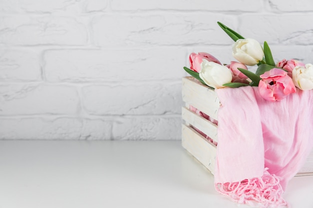 Nahaufnahme von rosa schal und von tulpen blühen innerhalb der hölzernen kiste auf schreibtisch gegen backsteinmauer