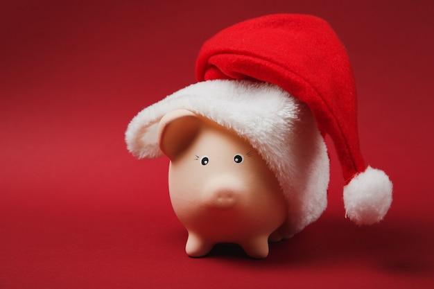 Nahaufnahme von rosa sparschwein mit weihnachtsmütze auf leuchtend rotem hintergrund isoliert. geldansammlung, investitionen, bank- oder geschäftsdienstleistungen, vermögenskonzept. kopieren sie platzwerbungsmodell.