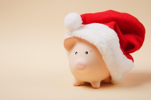 Nahaufnahme von rosa sparschwein mit weihnachtsmütze auf pastellbeigem hintergrund isoliert. geldansammlung, investitionen, bank- oder geschäftsdienstleistungen, vermögenskonzept. kopieren sie platzwerbungsmodell.