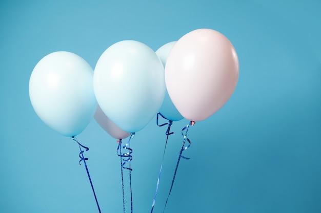 Nahaufnahme von rosa und blauen heliumballons auf blauer oberfläche mit weichen schatten und kopierraum