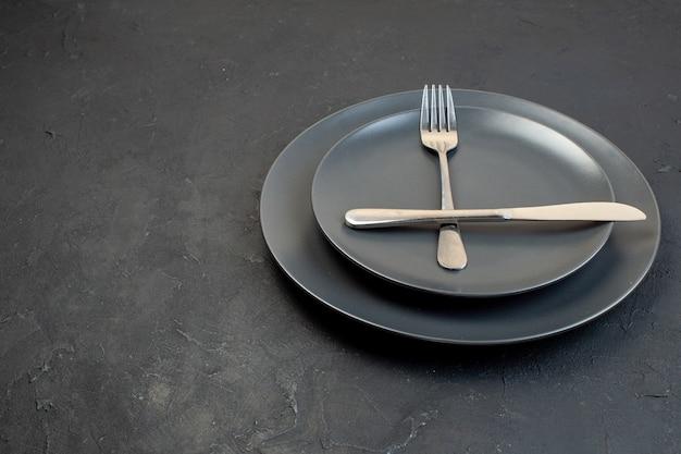 Nahaufnahme von rostfreiem besteck auf dunklen leeren tellern in zwei größen auf schwarzem hintergrund mit freiem platz
