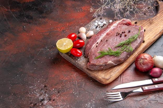 Nahaufnahme von rotem fleisch auf holzbrett und knoblauch grüne zitronenzwiebelgabel und messer auf dunklem hintergrund