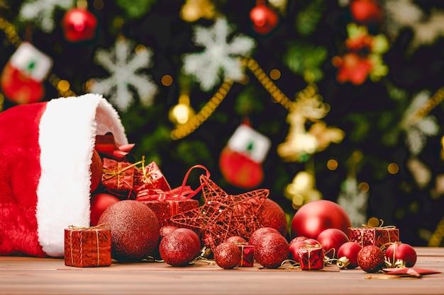 Nahaufnahme von roten dekorationsartikeln, sternkugel, geschenkboxen, die aus weihnachtsmütze auf holztisch vor schönem dekor mit eisflocken-socken-kiefer in unscharfem hintergrund gießen.
