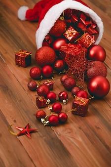 Nahaufnahme von roten dekorativen hängenden gegenständen mit glänzenden, glänzenden kugelbällen, bandfliege und geschenkboxen, die aus dem weihnachtsmann-weihnachtshut auf dunkelbraunem holztisch mit kopierraum strömen.